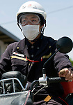 Postman Yoshinori Shoji sets off to deliver letters to an evacuation shelter at the Kadonowaki Junior High School in Ishinomaki, Miyagi Prefecture, Japan on Tuesday 24 May 2011..Photographer: Robert Gilhooly