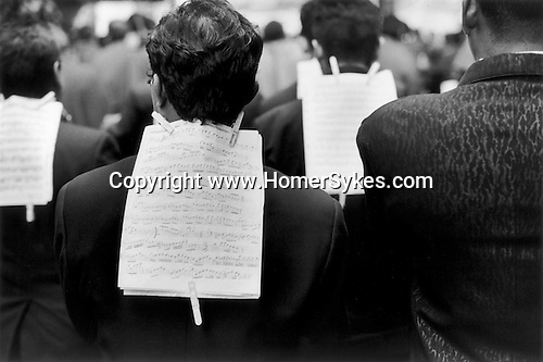 NEW YORK NEW YORK USA 1999. A  SAINTS DAYS PROCESSION THROUGH THE STREETS OF NEW YORK. THE ETHNIC  MUSICIAN'S WALKS DOWN A MIDTOWN STREET. A MUSICAL SCORE IS ATTACHED TO THE JACKET BACK OF EACH MEMBER OF THE BAND WITH CLOTH PEGS.