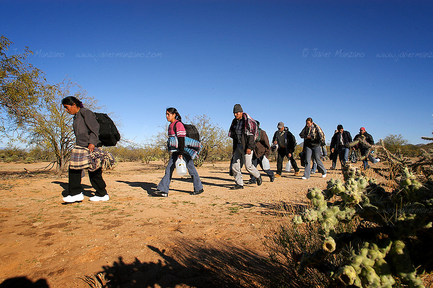 "A large group of Immigrants, guided by two ""coyotes"" or guides,  walk on the desert of Sonora bound for the border with Arizona. This group consisted of 37 border crossers, from four different countries- They included people from Mexico, Honduras, El Salvador and one Brazilian. .Sasabe, Mexico.  01/23/05"