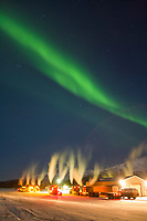 Aurora streams over Semi tractor trailer trucks at the Coldfoot truckstop in Coldfoot, Alaska.