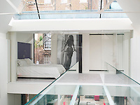 The bedroom at the back of the house connects to the bathroom and stairs via a glass bridge that crosses the atrium. Storage is discreetly tucked away while a doorway leads out to a roof terrace accessed via a spiral staircase