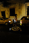 A woman and taxis on rainy night on a cobblestone street in Cartagena, Colombia.