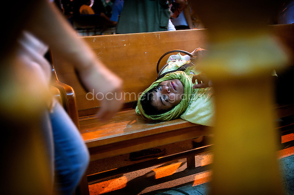 A woman in a trance lying on a bench waiting to recover.<br />