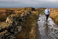 Woman running along a footpath on Wheelton Moor, near Brinscall, Lancashire