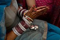 Delhi, India, 20 gennaio 2011. Matrimonio di Sumedha e Sapan. Durante le celebrazioni propiziatorie per la sposa.  A Sumedha viene fatta indossare una fila di bangles per ogni braccio. Essi rappresentano uno dei simboli più importanti dell'unione matrimoniale. Secondo la tradizione i bracciali andrebbero portati per un anno.