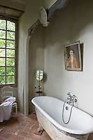 A free-standing roll top bath is placed in an alcove in this tiled bathroom