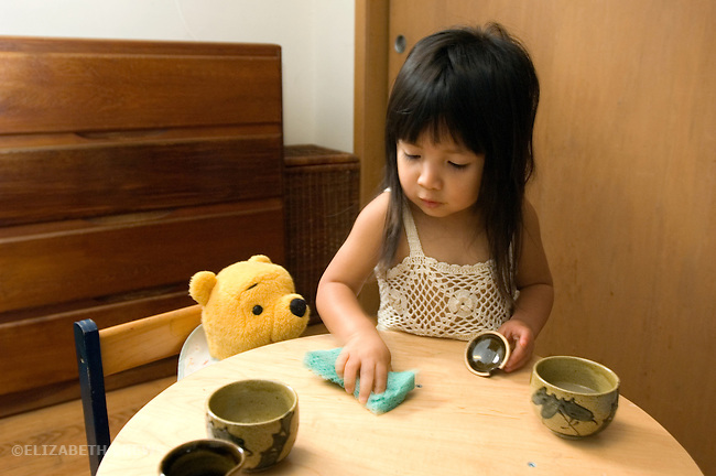 Berkeley CA Girl, age two and a half, Guatemalan, cleaning up spilled after party with bear MR
