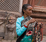 "A woman sells necklaces (some made of bone) in Kathmandu, the largest city in Nepal (700,000 people). Kathmandu is sometimes called ""Kantipur"". The original inhabitants of the Kathmandu Valley are Newars, who speak the language Nepal Bhasa. However, Nepali is the lingua franca of the valley and is the most widely spoken language. The city stands at an elevation of 6235 feet / 2230 meters."