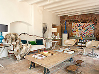 The living room is furnished with an eclectic mix of an 18th century sofa, a pair of vintage leather and chrome armchairs and a rustic oversized wooden coffee table