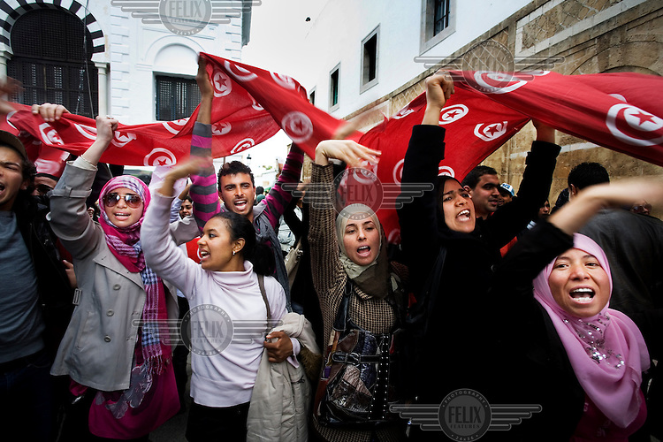 Women wave Tunisian flags during a demonstration in Kasbah Square, Tunis.