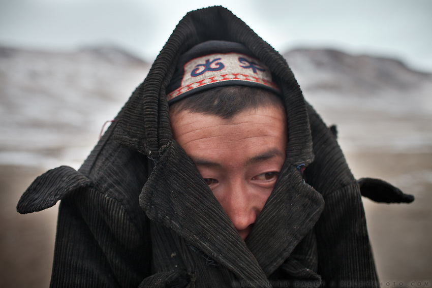 A Kyrgyz man keeps his ears sheltered from the infamous Bod-e Wakhan, the icy easterly wind of the Wakhan..In and around the camp of Ortobil, Manara (Sufi camp), near the borders with China and Tajikistan...Trekking with yak caravan through the Little Pamir where the Afghan Kyrgyz community live all year, on the borders of China, Tajikistan and Pakistan.