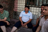 Uighur men wait outside their apartment in Urumqi.