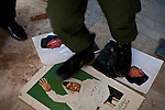 Members of a newly formed militia stamp on pictures of Gadaffi in Benghazi on Feb. 26, 2011.