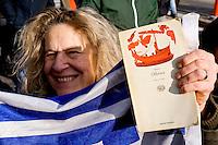Roma, 14 Febbraio  2015<br /> Manifestazione di solidariet&agrave; con la Grecia di Alexis Tsipras e contro le politiche di austerity imposte dalla troika. Manifestante con la bandiera greca e il libro Odissea di Omero<br /> Rome, February 14, 2015<br /> Demonstration of solidarity with Greece  of Alexis Tsipras and against austerity policies imposed by the Troika. Protestor with the Greek flag and the book Odyssey of Omero