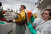 On his return to the Greenpeace ship Rainbow Warrior, videographer Jari Stahl undergoes radiation contamination checks conducted by radiation safety advisor Ike Teuling, after being at sea collecting sea water and seaweed samples to monitor radiation contamination levels. As the ship sails up the eastern coast of Japan, in the vicinity of Fukushima, in Japan, Tuesday 3rd May 2011.