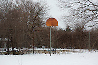 A rusty basketball hoop stands on the grounds of the Fernald Developmental Center in Waltham, Massachusetts, USA. Much of the campus has fallen into disrepair.