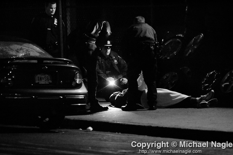 BROOKLYN  --  NOVEMBER 25, 2005:  Police investigate the shoot of an unidentified man, who recently immigrated from Jamaica, shot during a robbery while working at Gary?s Tire Emporium near 96th Street and Clackson Avenue on November 27, 2005 in Brooklyn.  The owner of the shop Gary Turner and his 17 year-old son were also shot.  Gary Turner died at Brookdale University Hospital and Medical Center.  (PHOTOGRAPH BY MICHAEL NAGLE).