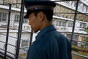 A prison warder makes his way through the fenced and grilled walkways connecting buildings, in Onomichi prison, Japan. May 19th 2008. The prison is operating at 106% capacity of prisoners, with just over 200 prisoners.