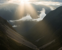 Beams of rising sun penetrate clouds over St. Arnaud Ranges, Nelson Lake National Park, South Island, New Zealand, NZ