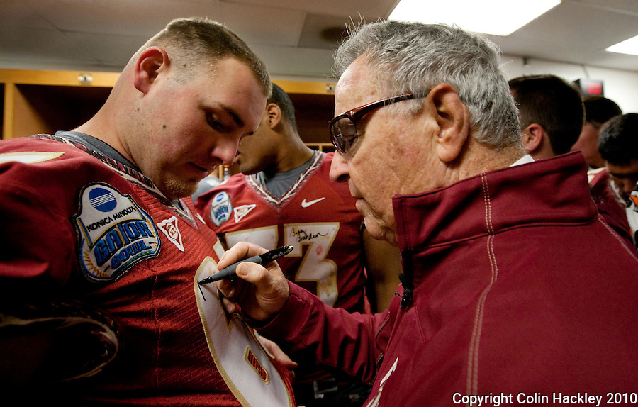 JACKSONVILLE, FL 1/1/10-FSU-WV FB CH105-Florida State Head Coach Bobby Bowden signs the jersey of AJ Ganguzza in the locker room after his final game in the Gator Bowl, Friday in Jacksonville, Fla. The Seminoles beat West Virginia 33-21..COLIN HACKLEY PHOTO