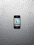 Apple iPhone 4 smartphone with desktop icons on its display isolated on wet shiny steel background. High quality photo.