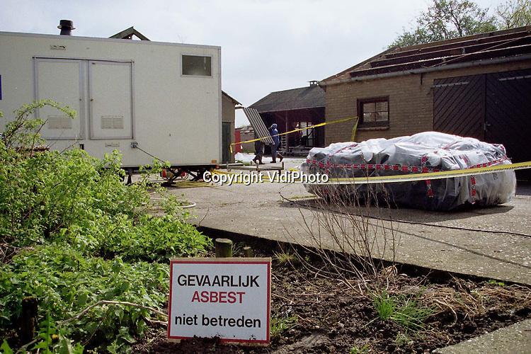 Foto: VidiPhoto..HERVELD - Werknemers van een gespecialiseerd bedrijf verwijderen asbestplaten van het dak van een boerenschuur. Ze zijn voorzien van beschermende kleding. Ook in de bedrijfswoning zelf bevindt zich het gevaarlijke goedje. Het boerenbedrijf aan de Sierakkerstraat in Herveld moet gesloopt worden om de komst van de Betuwelijn mogelijk te maken. Voordat .het zover is dient eerst het gevaarlijke materiaal verwijderd te worden. Daar is men deze week mee begonnen. Asbest is een probleem waar de NS bij de .sloop van gebouwen op de route diverse keren mee in aanraking komt. Volgens een woordvoerster van de Spoorwegen zorgt dat echter niet voor extra vertraging van de werkzaamheden, omdat hier tijdens het vooronderzoek al rekening mee is gehouden. Over de (extra) kosten die de asbestverwijdering met zich meebrengt, weigert de NS informatie te geven..