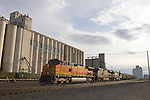 An eastbound BNSF grain train passes the towering grain elevator at Hereford, TX as storms approach.