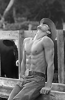 handsome cowboy outdoors on a fence