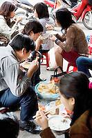 Vietnam. Hanoi. Early morning on a street's restaurant, a group of men and women, seated on small plastic stools, eat for breakfast a bowl of beef noodle soup, called pho. The pho is a traditional dish of Vietnam. People eat with chopsticks which are a pair of small, equal-length, tapered sticks, used as traditional eating utensils. 08.04.09 © 2009 Didier Ruef