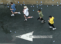 Four runners follow road markings while running a 10k road race in Charlottesville, Va. run race exercise