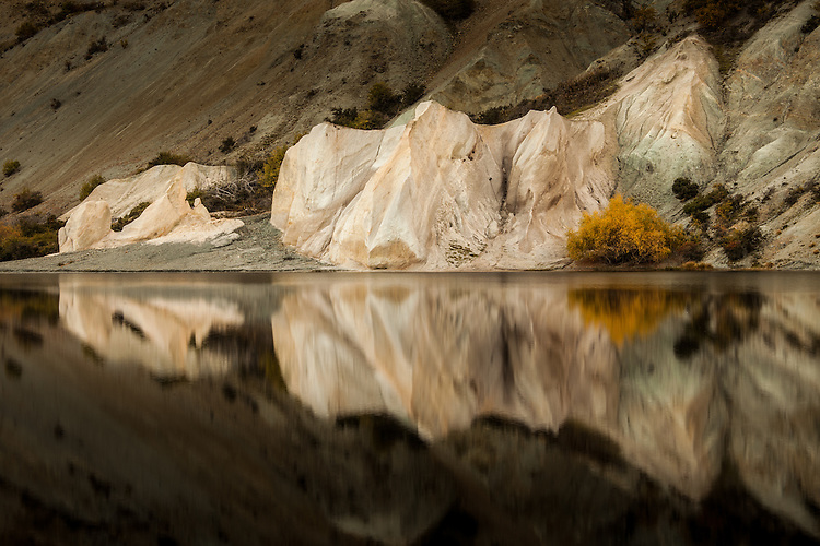 Limestone cliffs & autumn willow tree reflection. Blue Lake at St Bathans, Central Otago, South Island, New Zealand. Stock photo, canvas, fine art print