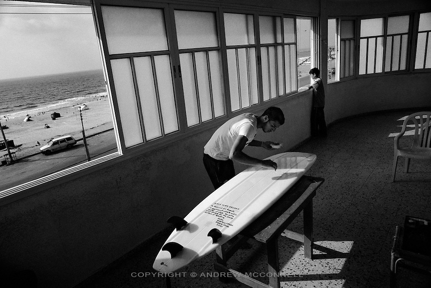 Mahmoud Alryashi makes repairs to his surfboard at his home in Gaza City, Gaza. Nearly all of the surfboards in Gaza have been donated from outside, mainly the United States.