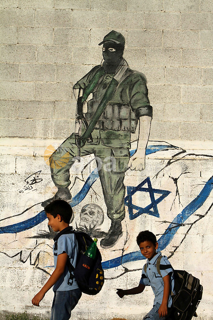 Palestinian boys walk past a graffiti depicting a Palestinian militant stepping on skulls and the Israeli flag in Gaza City, a day before a prisoner swap between Israel and Hamas, Monday, Oct. 17, 2011. Photo by Ashraf Amra