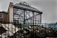 New Caledonia Glasshouse (formerly The Mexican Hothouse), 1830s, Charles Rohault de Fleury, Jardin des Plantes, Museum National d'Histoire Naturelle, Paris, France.  Low angle view from the Plant History Glasshouse (formerly the Australian Glasshouse), showing the rubble from the renovation works in the foreground. The New Caledonia Glasshouse, or Hothouse, was the first French glass and iron building.