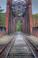 Railroad tracks run to and over the top deck of the historic Free Black Bridge, a through truss pin-connected bridge over the Androscoggin River on the Maine Central Railroad in Brunswick, Maine