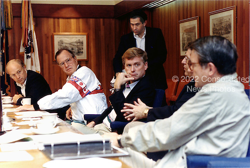 """Camp David, Maryland - August 4, 1990 -- United States President George H.W. Bush meets with national security advisors at Camp David to discuss Iraq on August 4, 1990.  From left ate Secretary of Defense Richard B. """"Dick"""" Cheney; President Bush;  Vice President Dan Quayle; Defense Undersecretary Paul D. Wolfowitz (standing); White house Chief of Staff John Sununu; and Central Intelligence Agency (CIA) Director William H. Webster..Credit: White House via CNP"""