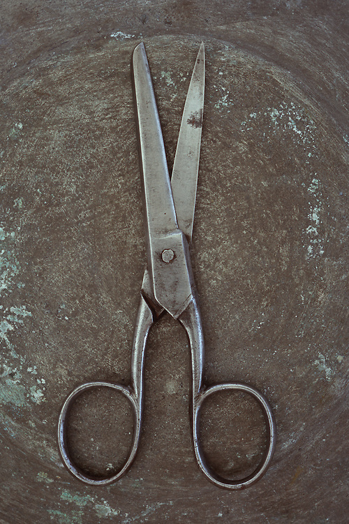 Vintage steel kitchen scissors lying slightly open on tarnished metal
