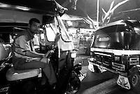 A tuk tuk driver at night in the streets of Mumbai, India