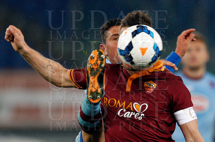 Calcio, Serie A: Roma vs Torino. Roma, stadio Olimpico, 25 marzo 2014.<br /> AS Roma forward Francesco Totti has his face hidden by the ball as he is challenged by Torino midfielder Giuseppe Vives, left, during the Italian Serie A football match between AS Roma and Torino at Rome's Olympic stadium, 25 March 2014.<br /> UPDATE IMAGES PRESS/Riccardo De Luca