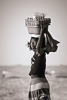 A rural woman is selling boiled eggs as a snack on the beach at Mussulo