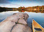 Canoe at a rocky shore of lake George. Beautiful sunset fall nature scenery. Killarney Provincial Park, Ontario, Canada.