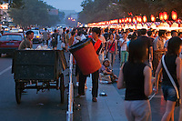 Men collecting rubbish at the Wangfujing night markets, Beijing, China.