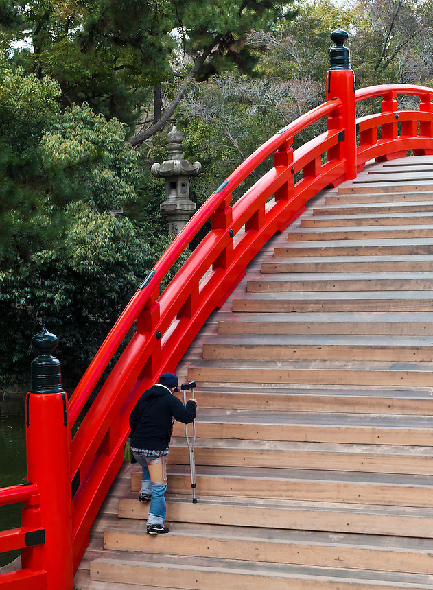 An injured person on a crutch climbs the very steeply arched bridge to enter the Tsumiyoshitaisha shrine to pray.