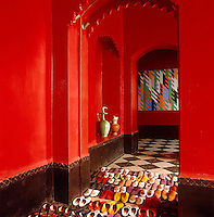 Rows of colourful Moroccan slippers on the black and white tiled floor of this red entrance hall are reflected in a large mirror