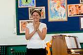 Teacher applauds after concert for parents, Open Day at State Junior School..