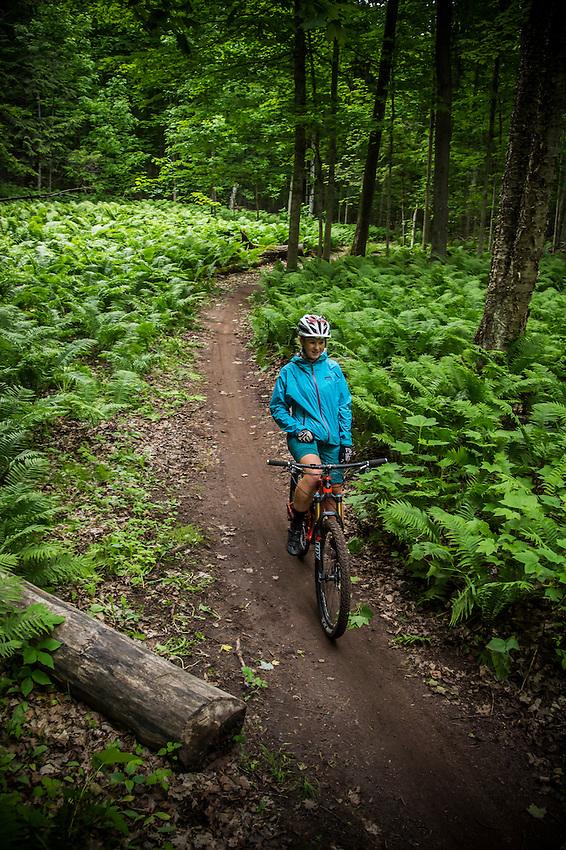 A female mountain biker rides the Noquemanon Trails Network's Gorgeous Trail along the Carp River in Marquette, Michigan.