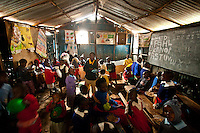 Nairobi, June 2010 -  the younger kids break for lunch in their one-room school at the St. Catherine's children's home in the Kibera slum.