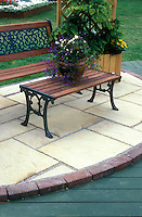 Stone paver patio edged in brick next to wood decking, with patio furniture and container of plants 7431