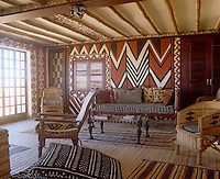 African fabrics and furniture have been used to dramatic effect in this living room where contrasting patterns and motifs are given cohesion within a strict colour scheme