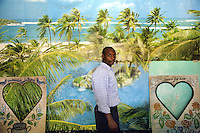 Rwanda. Southern province. Gitarama. District of Muhanga. Portrait of a black man inside a photo studio. He stands close to a giant poster of a fake tropical holiday paradise with the sea, a white sand beach, palm trees, an island,.... © 2007 Didier Ruef